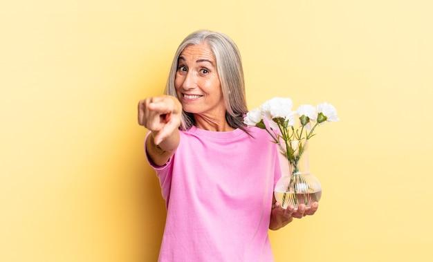 Apontando para a câmera com um sorriso satisfeito, confiante e amigável, escolhendo você segurando flores decorativas