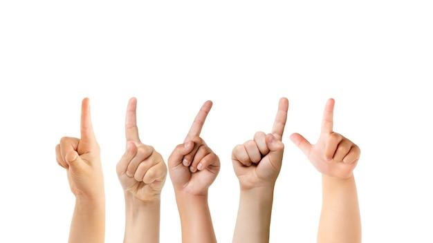 Apontando para cima. mãos de crianças gesticulando isoladas no fundo branco do estúdio, copyspace para anúncio. multidão de crianças gesticulando. conceito de infância, educação, pré-escola e tempo escolar. sinais e sentidos.