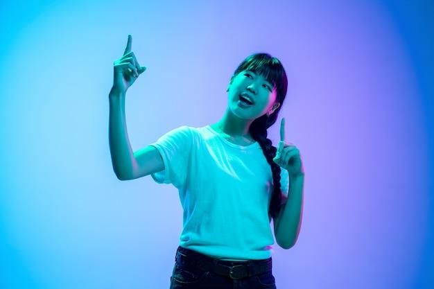 Apontando para cima. retrato da jovem mulher asiática em fundo gradiente estúdio azul-roxo em luz de néon. conceito de juventude, emoções humanas, expressão facial, vendas, anúncio. bela modelo moreno.