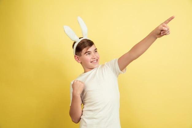Apontando para o lado. menino caucasiano como um coelhinho da páscoa em fundo amarelo do estúdio. saudações de páscoa feliz. lindo modelo masculino. conceito de emoções humanas, expressão facial, feriados. copyspace.