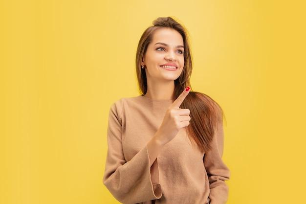 Apontando. retrato de jovem mulher branca isolada em amarelo