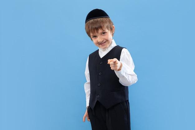 Apontando. retrato de um jovem rapaz judeu ortodoxo isolado na parede azul. purim, negócios, festival, feriado, infância, celebração pessach ou páscoa, judaísmo, conceito de religião.