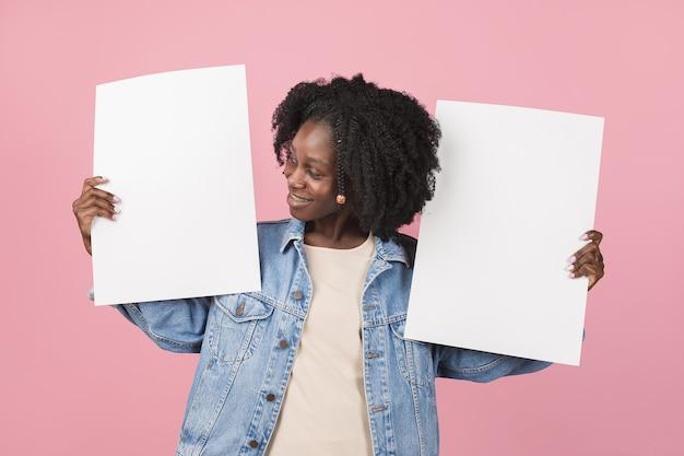 Apontando. retrato de uma linda mulher afro-americana isolado na parede rosa com copyspace. modelo feminino elegante. conceito de emoções humanas, expressão facial, moda, juventude.