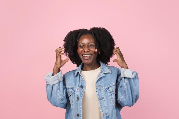 Apontando. retrato de uma linda mulher afro-americana isolado na parede rosa com copyspace. modelo feminino elegante. conceito de emoções humanas, expressão facial,
