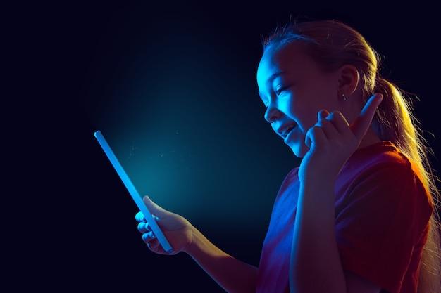 Apontando, rindo. retrato da menina caucasiana na parede escura em luz de néon. bela modelo feminino usando tablet. conceito de emoções humanas, expressão facial, vendas, anúncio, tecnologia, dispositivos.