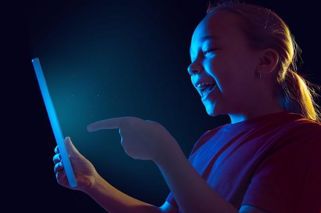 Apontando, rindo. retrato da menina caucasiana na parede escura em luz de néon.