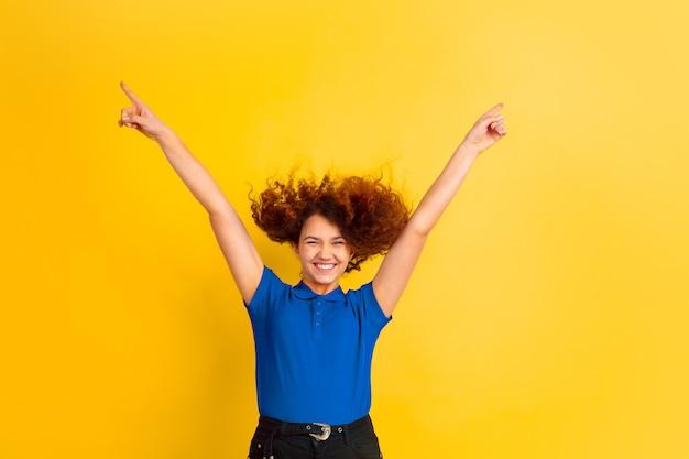 Apontando, rindo. retrato de menina adolescente caucasiano em fundo amarelo do estúdio. linda modelo feminino encaracolado com camisa azul. conceito de emoções humanas, expressão facial, vendas, anúncio. copyspace.