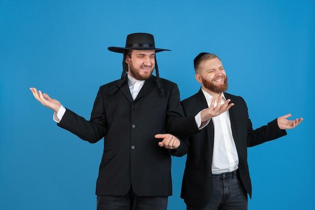 Apontando, saudando. retrato de um jovem judeu ortodoxo isolado na parede azul. purim, negócios, festival, feriado, celebração pessach ou páscoa, judaísmo, conceito de religião.