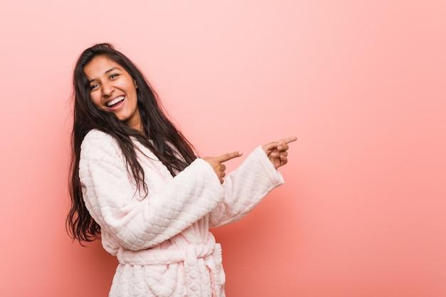 Apontar entusiasmado vestindo do pijama indiano novo da mulher com dedo indicador afastado.