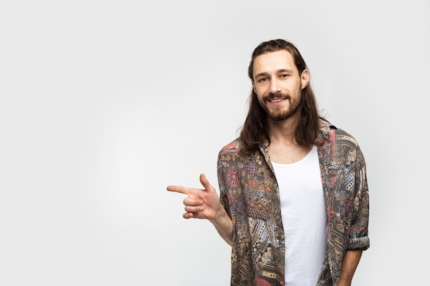 Aponte o dedo para o lado para colocar texto, logotipo ou anúncio. hipster viajante despreocupado elegante homem sobre um fundo branco studio, estilo de vida as pessoas