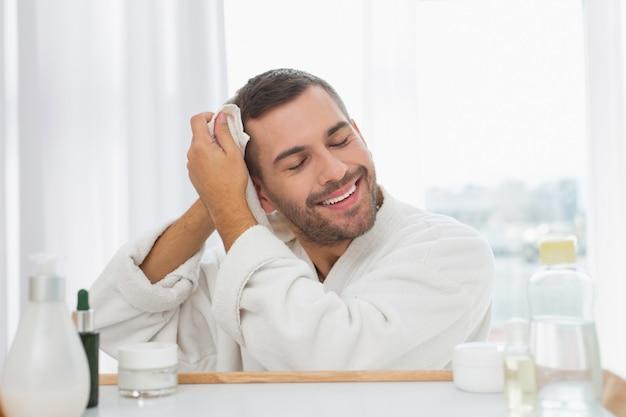 Após o banho. homem bom e feliz sorrindo enquanto está após o banho