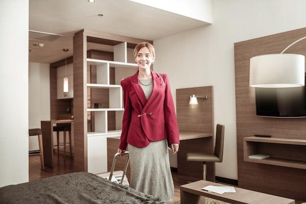 Após um vôo bem-sucedido. mulher loira bem sucedida olhando para seu quarto de hotel após um voo bem sucedido