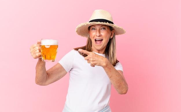 Aposentada bonita de meia-idade bebendo cerveja nos feriados