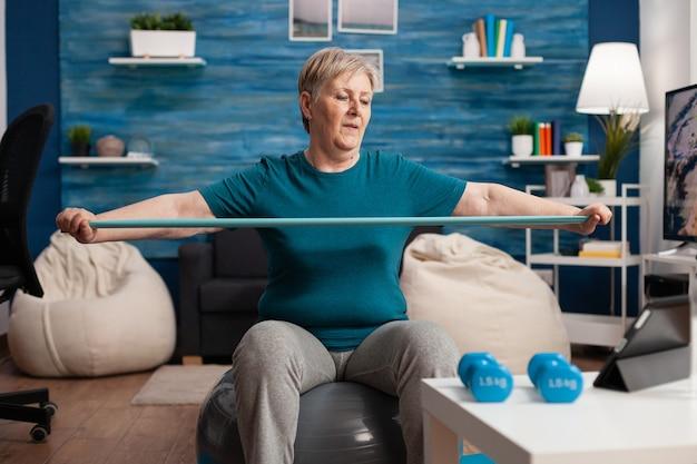 Aposentado alegre aposentado sentado na bola suíça assistindo a um vídeo de fitness no tablet alongando o braço usando um elástico durante o treino de saúde na sala de estar