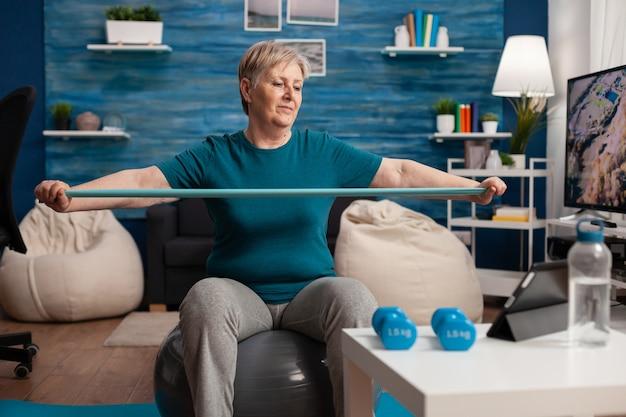 Aposentado alegre aposentado sentado na bola suíça assistindo a um vídeo de fitness no tablet esticando o braço ...
