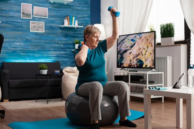 Aposentado aposentado concentrado sentado na bola suíça de fitness levantando o músculo do braço e alongando a mão fazendo exercícios de saúde