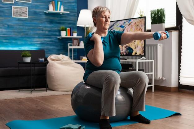 Aposentado atlético em roupas esportivas assistindo a exercícios aeróbicos on-line usando um tablet sentado na bola suíça ...