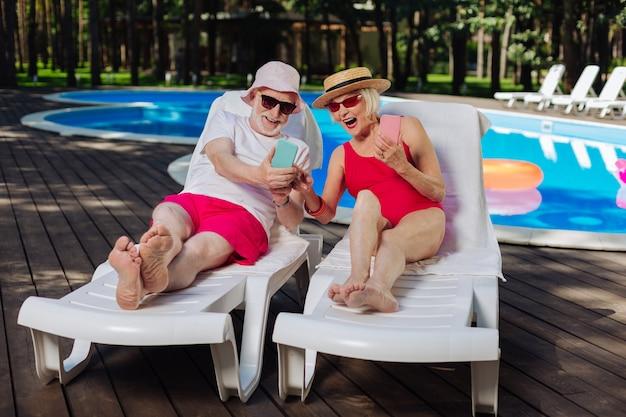 Aposentado barbudo mostrando um vídeo engraçado em seu telefone, sua esposa moderna e elegante