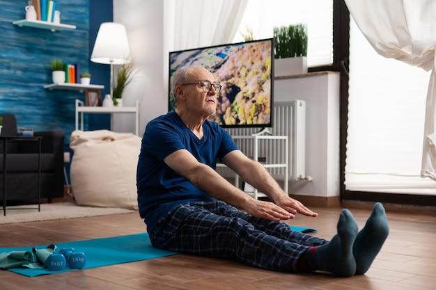 Aposentado focado em roupas esportivas, sentado em um tapete de ioga, alongando os músculos das pernas durante exercícios aeróbicos, exercitando a resistência dos músculos