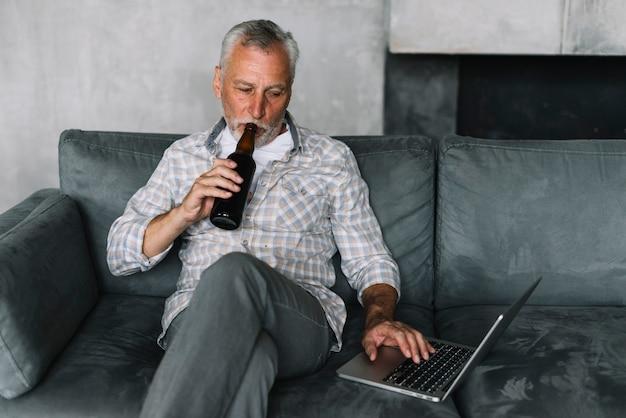 Aposentado homem beber cerveja de garrafa usando laptop
