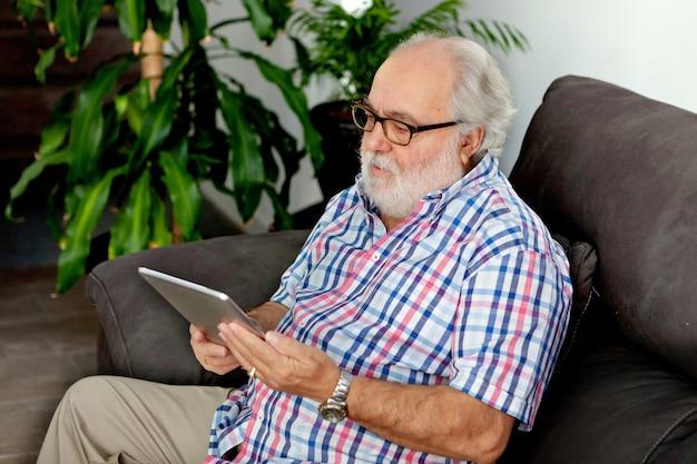 Aposentado homem com barba branca, procurando um tablet em sua casa