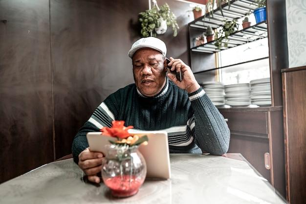 Aposentado homem negro usando a tecnologia está sentado na cafeteria usando seu tablet e celular conectado por wifi