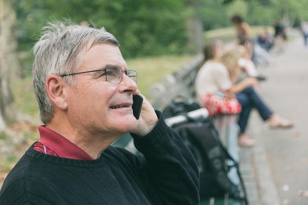 Aposentado homem sênior no parque, falando no celular, sorrindo a expressão