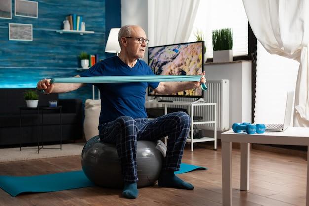 Aposentado inválido praticando exercícios ativos para os braços usando elástico de resistência assistindo a vídeos de exercícios físicos online no laptop