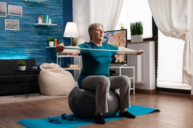 Aposentado sentado na bola suíça, trabalhando no peso corporal, alongando o braço muscular usando um elástico de fitness