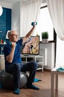 Aposentadoria sênior sentado na bola suíça de aeróbica levantando os músculos do braço, fazendo alongamento