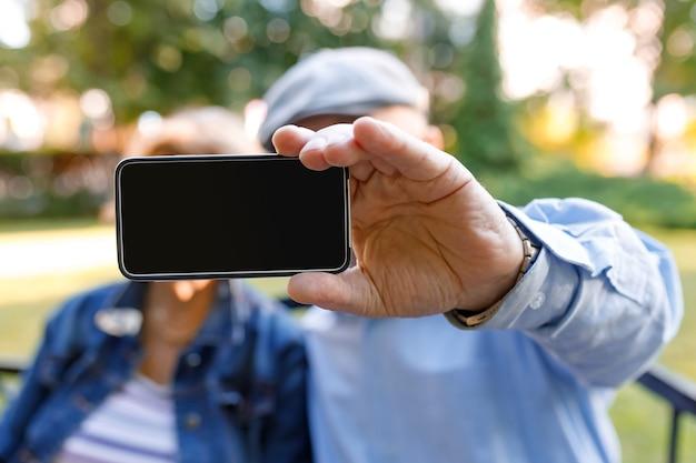 Aposentados irreconhecíveis que usam tecnologias modernas e mostram uma tela de telefone em branco