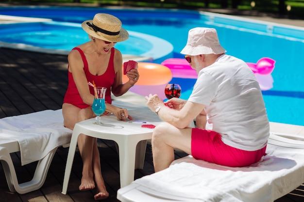 Aposentados modernos se divertindo enquanto jogam cartas sentados perto da piscina