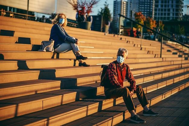 Aposentados sentados na escada e usando máscaras protetoras.