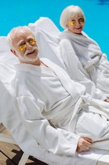 Aposentados usando tapa-olhos e roupões de banho brancos, deitados perto da piscina, desfrutando de um ambiente tranquilo