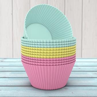 Aposta de copos de silicone cupcake colorido em uma mesa de madeira. renderização 3d Foto Premium