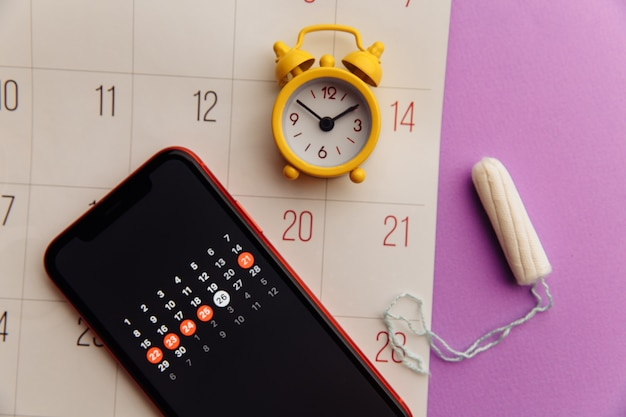 App de menstruação em smartphone com tampão de algodão e despertador amarelo. dias críticos de mulher e o conceito de proteção de higiene.