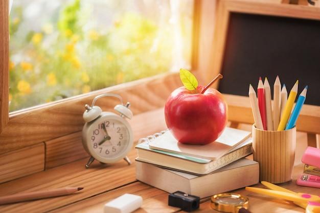 Apple colocou em um livro com equipamento educacional perto da janela para a luz da manhã, conceito de volta às aulas e espaço de cópia