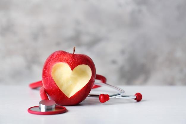 Apple com estetoscópio na cor de fundo