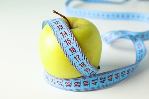 Apple com fita métrica em fundo branco, close-up