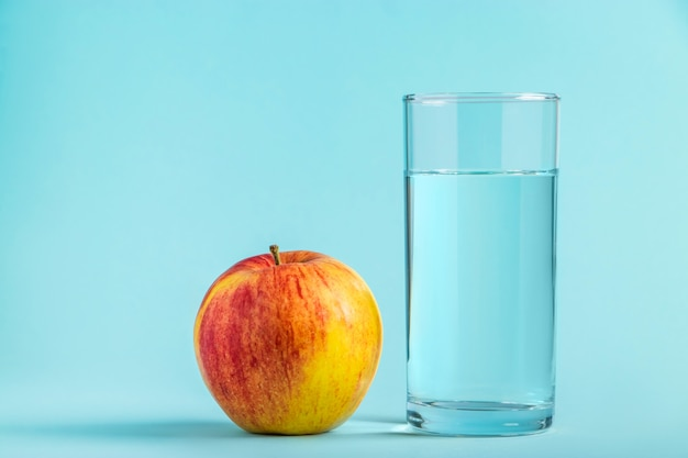 Apple e copo de água pura em um espaço azul. conceito de saúde e dieta alimentar