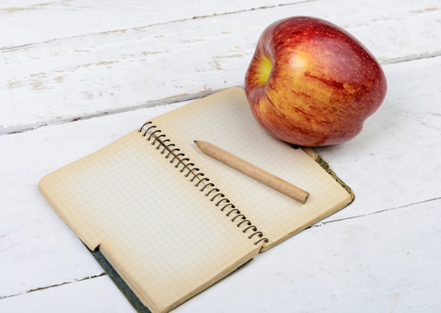 Apple e notebook em uma mesa