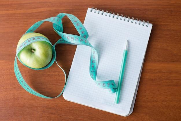 Apple e um caderno em um fundo de madeira. saúde
