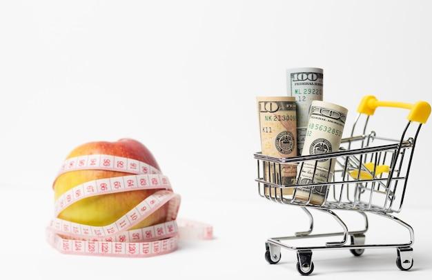 Apple embrulhado em um centímetro. carrinho de compras com dinheiro.