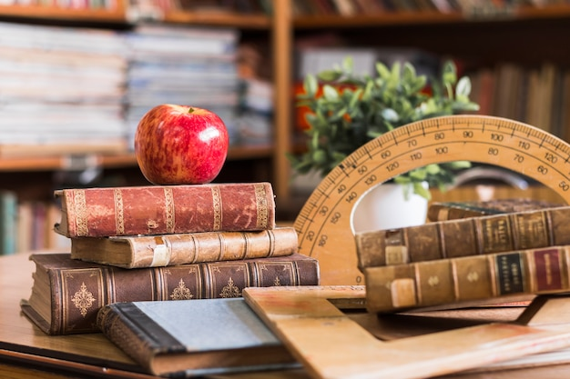 Apple perto de livros e ferramentas de geometria