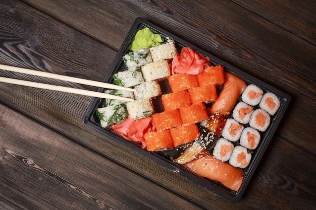 Aprecie sushi de comida asiática com palitos para cortar