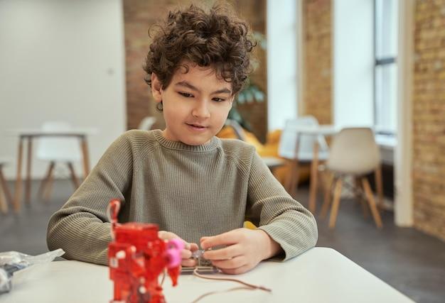 Aprenda como funciona adorável garotinho sentado à mesa checando brinquedos técnicos cheios de detalhes