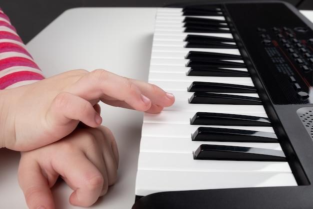 Aprendendo a tocar piano, a garotinha mãos nas teclas do sintetizador.