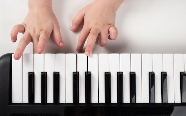 Aprendendo a tocar piano, menina mãos em closeup de teclas de sintetizador.