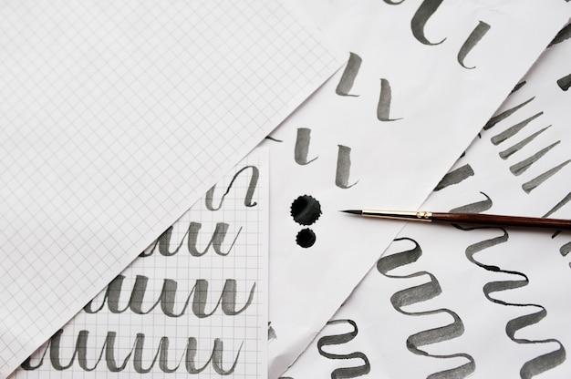 Aprendendo caligrafia - papel com exemplo e pincel e tinta