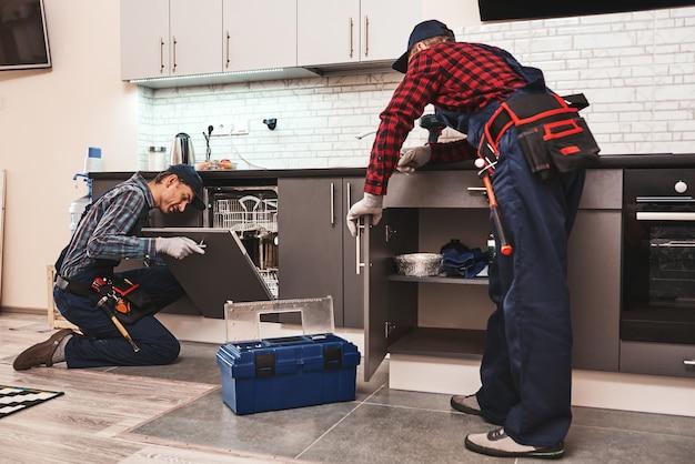 Aprendendo com o melhor técnico de dois homens sentado perto da máquina de lavar louça